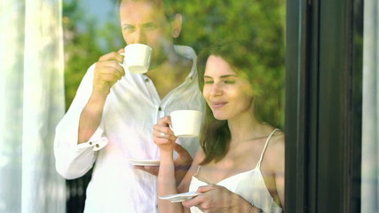 Young couple talking and drinking morning coffee by the window