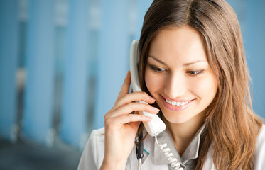 Young doctor on phone, at office