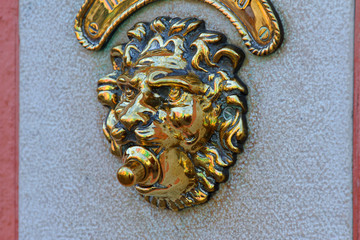door bell in the shape of a golden lion