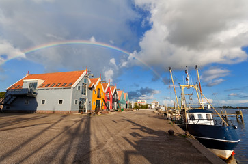 rainbow over harbor in fishing village Zoutkamp
