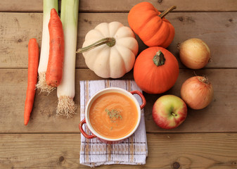 Homemade pumpkin soup on wood background