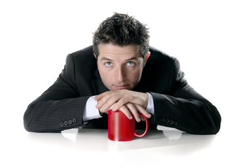 attractive business man in suit with red mug or cup of coffee