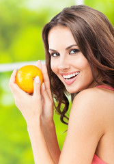 Young woman with orange, outdoors