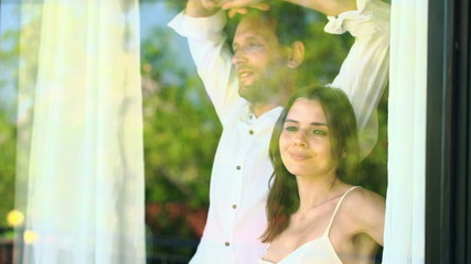 Couple in love unveil curtains by the window