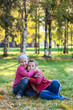 Laughing children embracing on the grass in the autumn park