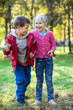 Brother and sister laughing when standing full length in park