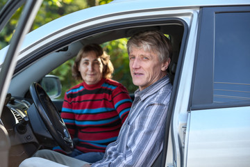 Mature husband and wife sitting in land vehicle, through door