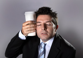 sleepy caffeine addict businessman holding take away coffee