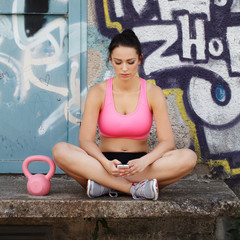 Sporty woman with kettlebell and smartphone