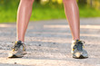 Legs of young sport woman staing on the road