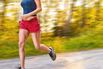 Young sport woman runs on the road