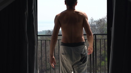 Man unveil curtains, walk out on terrace, enjoying morning