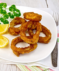 Calamari fried with lemon and fork on plate and napkin