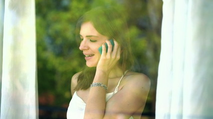Young woman talking on cellphone by the window