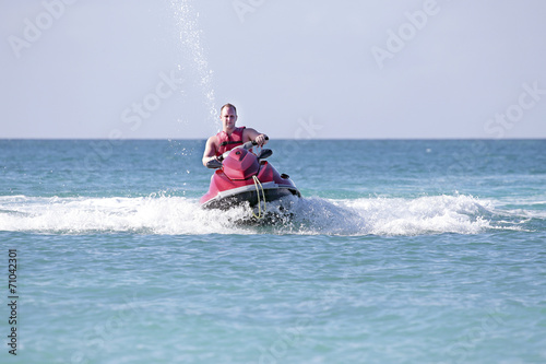 Fotobehang Water Motorsp. Young guy cruising on the caribbean sea on a jet ski