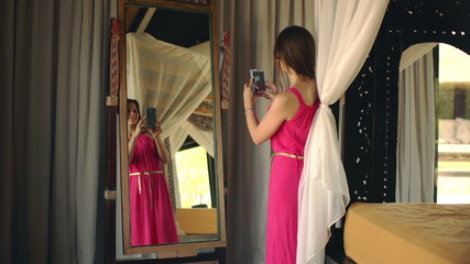 Beautiful woman taking selfie photo in front of the mirror