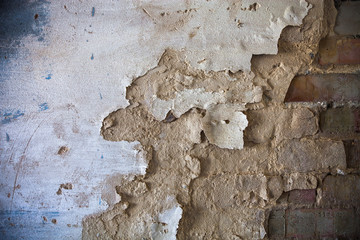 Damaged whitewashed plaster on the brick wall