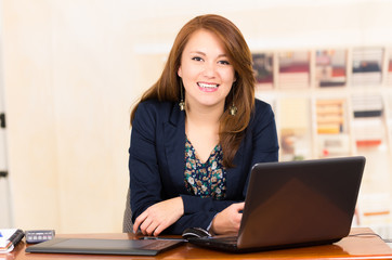 Beautiful young girl working behind a desk with laptop