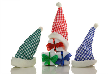 Drei Nikolausmützen mit Geschenken vor weißem Hintergrund