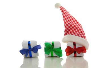 Weihnachtsgeschenke mit Nikolausmütze vor weißem Hintergrund