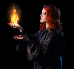 Young witch with flame isolated