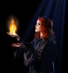 Witch with flame on blue rays background