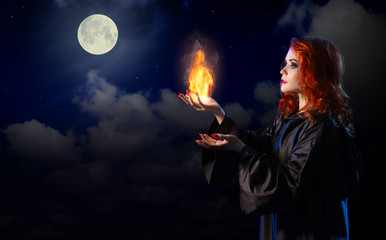 Witch with flame on night sky background
