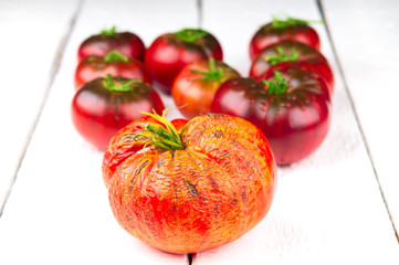 Spoiled and ripe tomatoes on white wooden background