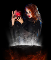 Young witch with red potion and cauldron