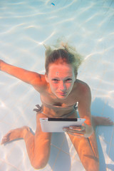 Young woman undewater with tablet computer