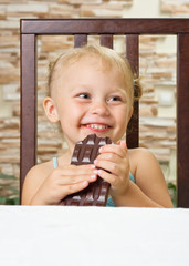 Little girl with chocolate at light room