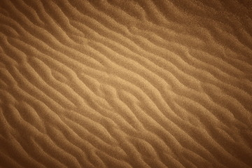 Golden wavy beach sand texture with vignette.
