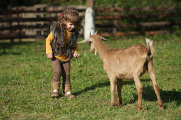 cute little girl plays with goat