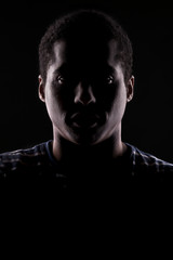african man with the face in shadow on a dark background