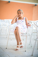 girl sitting on a chair of empty chairs