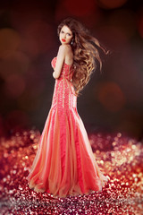 Beautiful glam with long hair posing in red dress over bokeh bri
