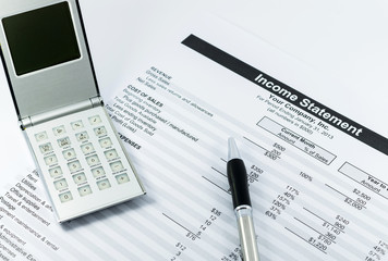 income statement report with calculator and pen for business