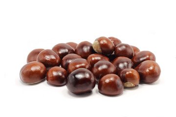 a handful of brown chestnuts on white background
