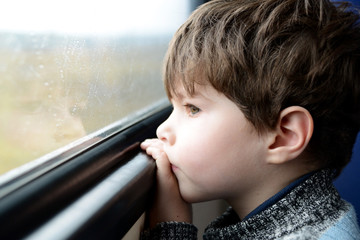 boy looking out the window on the train