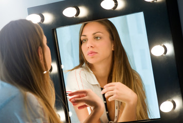 Young woman admiring herself in the mirror