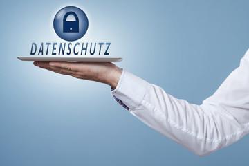 Hand hält Tablet darüber das Wort Datenschutz und Symbol Schloss