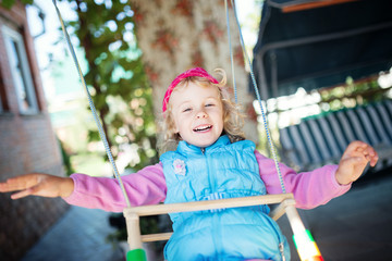 Laughing little girl on swing