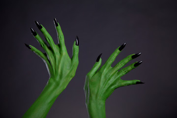Green monster hands with black nails, real body-art