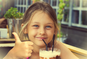 little girl drinking a chocolate milkshake and shows thumb