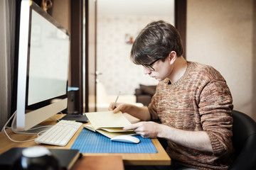 Young man at home using a computer, freelance developer or desig