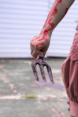 Woman holding knife with blood dripping