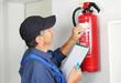 Leinwanddruck Bild - Fachmann bei der Prüfung eines Feuerlöschers