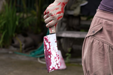 Woman with blood dripping holding device