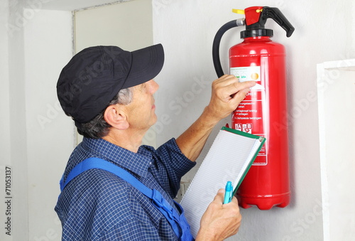 Leinwanddruck Bild Fachmann bei der Prüfung eines Feuerlöschers