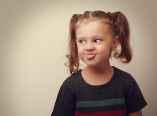 Happy fun cute kid girl showing the tongue. Closeup vintage